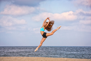 Ballet dancer jumping on the beach
